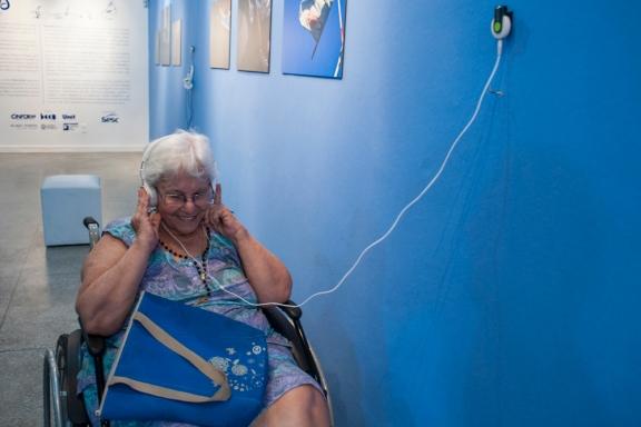 Rita Peixe ouve o próprio depoimento durante a exposição.
